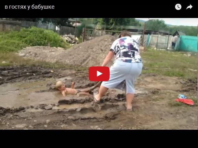 Бабушка вытаскивает внука из лужи за ногу. В гостях у бабушки